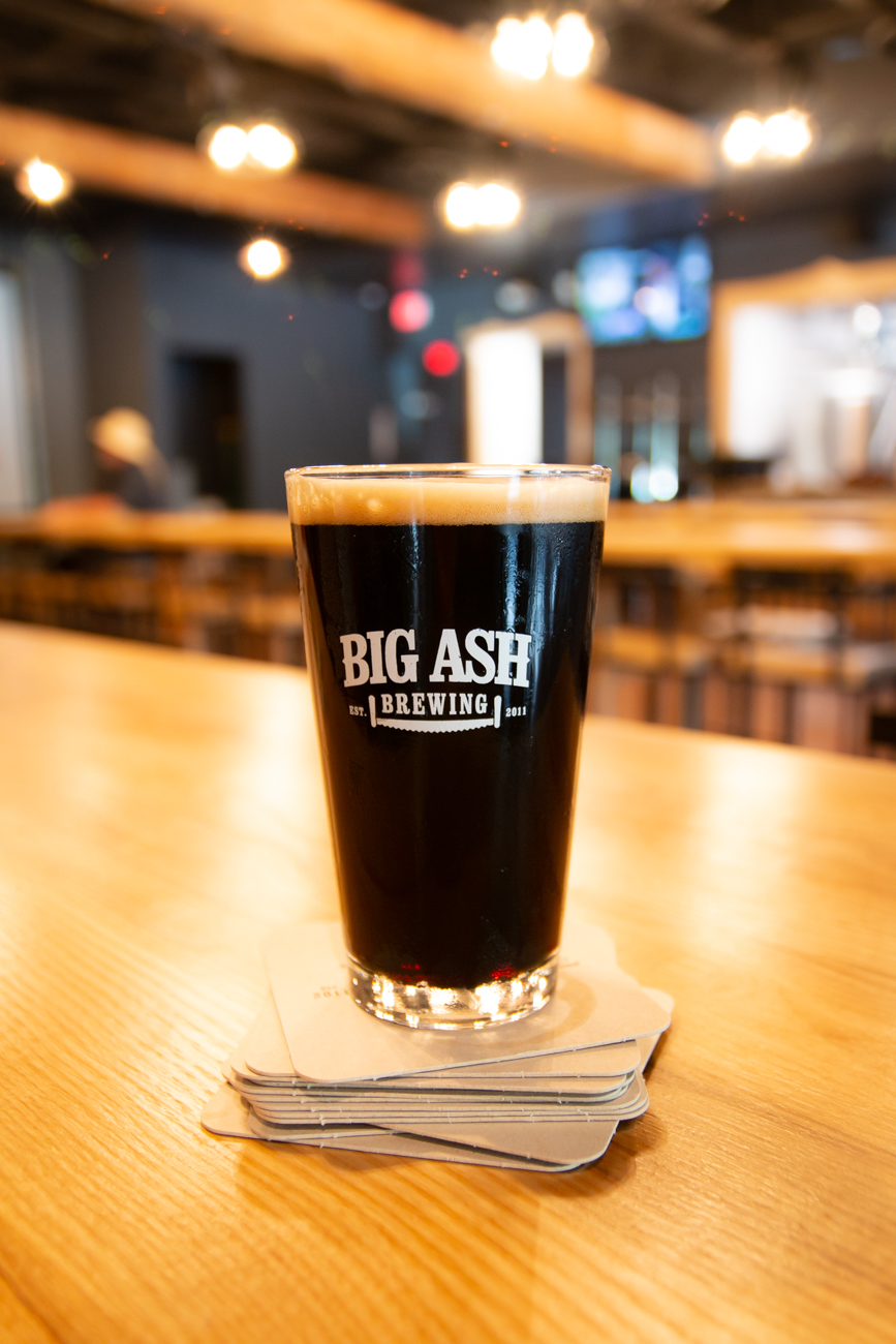 "In the early 2000s, Dave Emery, who's now a managing partner for Big Ash, started making batches of beer out of his home with a few friends just for fun. By 2011, the hobby grew to include 25 other brewers, all of whom chipped in $200, bought a bunch of equipment and ingredients, and formed a ""fraternal craft brew co-op."" The group decided in 2017 that they wanted to pursue a brick and mortar for their brews, but one that evaded issues in most breweries such as long lines at the bar and not getting to try as many beers as patrons want. / Image: Elizabeth A. Lowry // Published: 9.25.19"