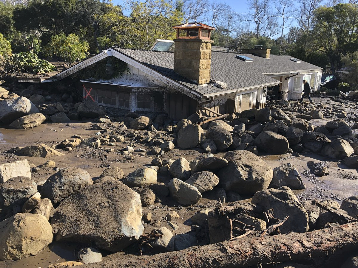 In this photo provided by Santa Barbara County Fire Department, Kerry Mann navigates the large boulders and mudflow that destroyed the home of her friend in Montecito, Calif., Wednesday, Jan. 10, 2018. The woman who lives in the home has not been seen since the early hours of Tuesday. (Mike Eliason/Santa Barbara County Fire Department via AP)