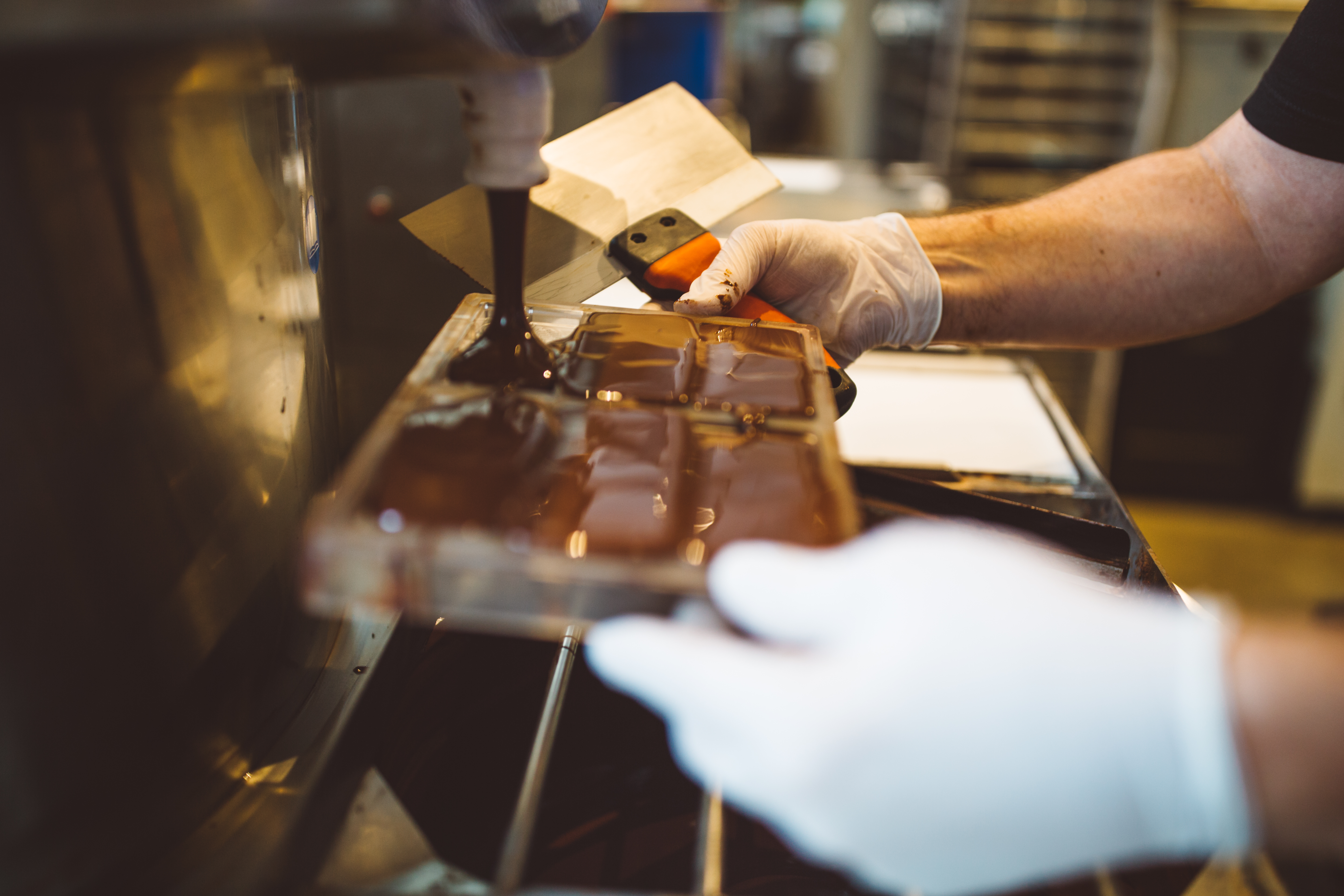 <p>The refined chocolate is then tempered, where it acquires its shiny and snappy characteristics.  Once it has been adequately tempered, the chocolate is finally poured into a desired mold. Vibration is used to get out any air bubbles, and the chocolate is then cooled until it hardens. (Image: Ryan McBoyle / Seattle Refined)</p>