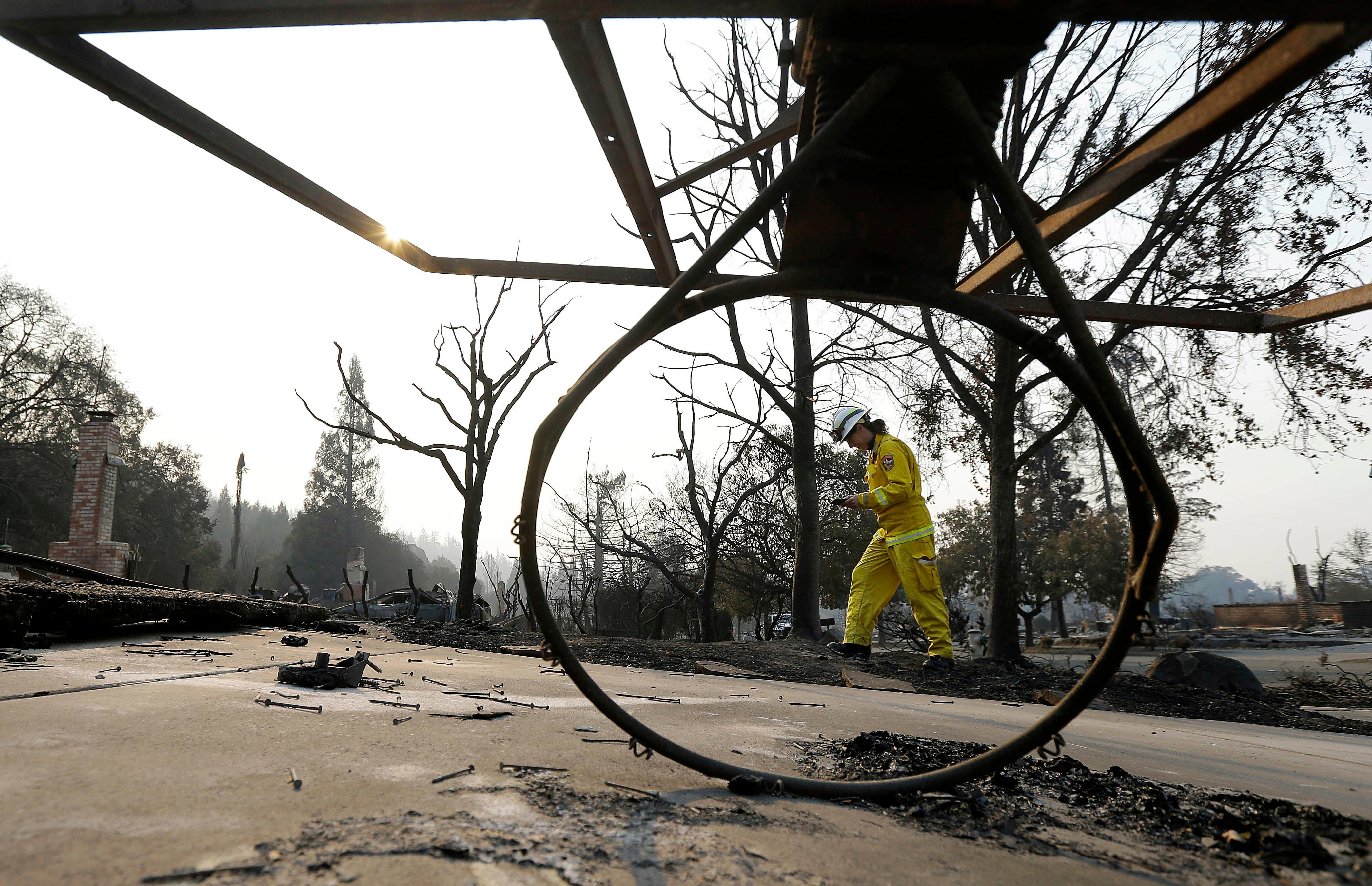Cal Fire forester Kim Sone is framed by a fallen basketball hoop as she inspects damage at homes destroyed by wildfires in Santa Rosa, Calif., Thursday, Oct. 12, 2017. Gusting winds and dry air forecast for Thursday could drive the next wave of devastating wildfires that are already well on their way to becoming the deadliest and most destructive in California history. (AP Photo/Jeff Chiu)