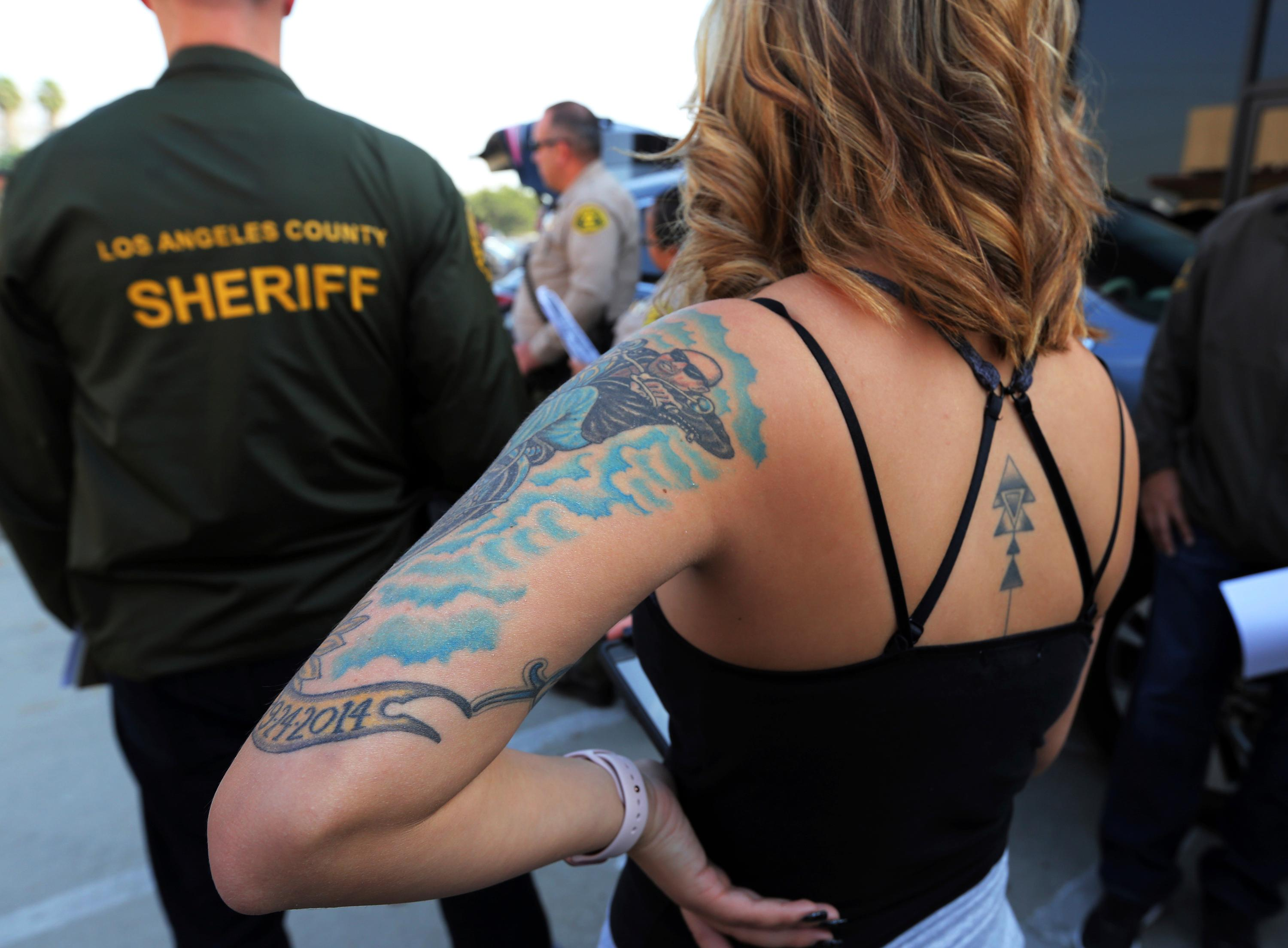 In this Wednesday, Nov. 15, 2017 photo, before an undercover sting operation, a sheriff's deputy who will pose as a prostitute listens at a briefing in Compton, Calif., a city some 15 miles south of Los Angeles.  (AP Photo/Reed Saxon)