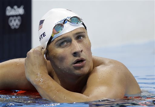 FILE - In this Tuesday, Aug. 9, 2016, file photo, United States' Ryan Lochte checks his time in a men's 4x200-meter freestyle heat during the swimming competitions at the 2016 Summer Olympics, in Rio de Janeiro, Brazil. Lochte and three other American swimmers were robbed at gunpoint early Sunday, Aug. 14, by thieves posing as police officers who stopped their taxi and took their money and belongings, the U.S. Olympic Committee said. (AP Photo/Michael Sohn, File)