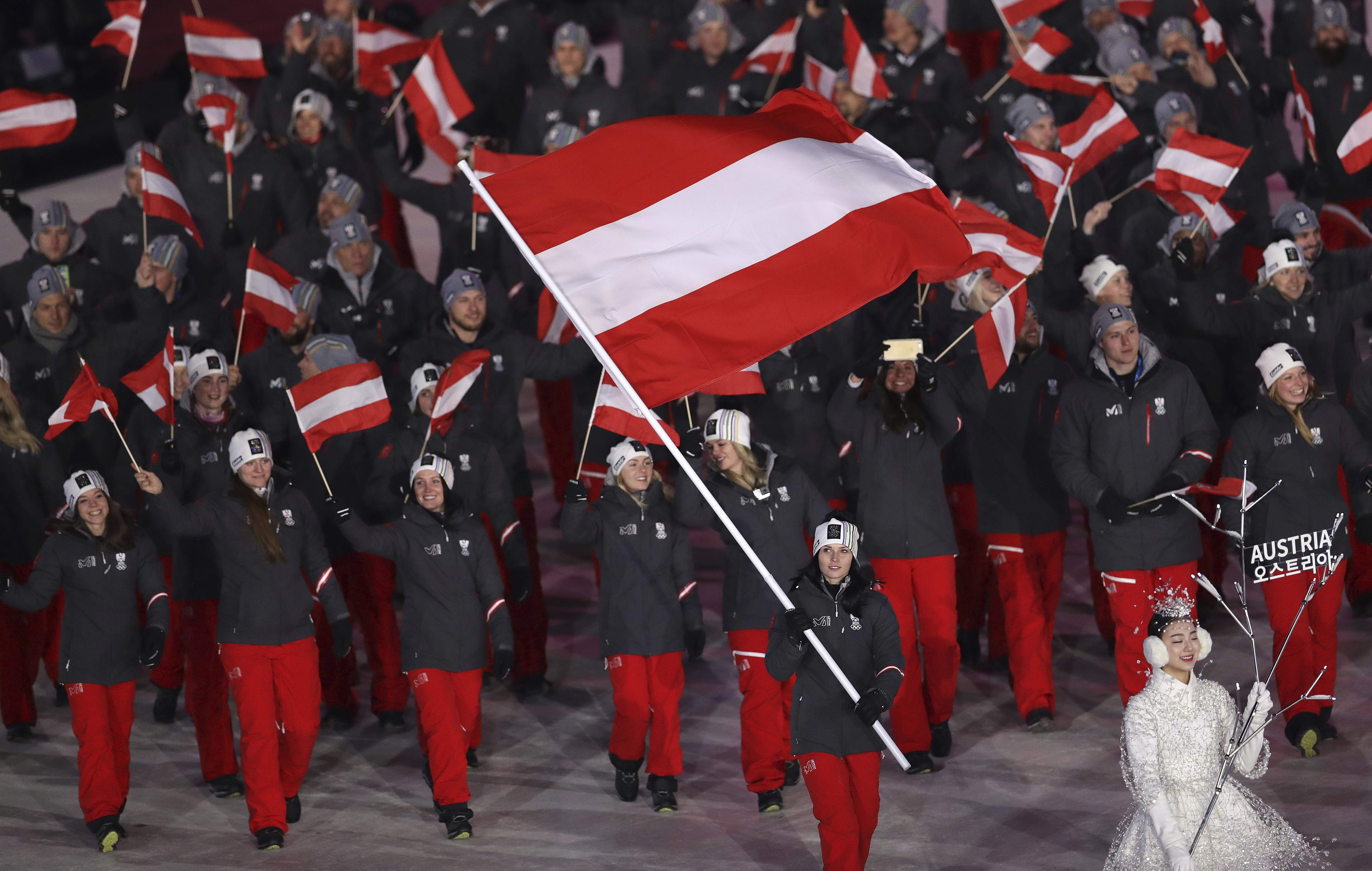 Anna Keith carries the flag of Austria during the opening ceremony of the 2018 Winter Olympics in Pyeongchang, South Korea, Friday, Feb. 9, 2018. (AP Photo/Michael Sohn)