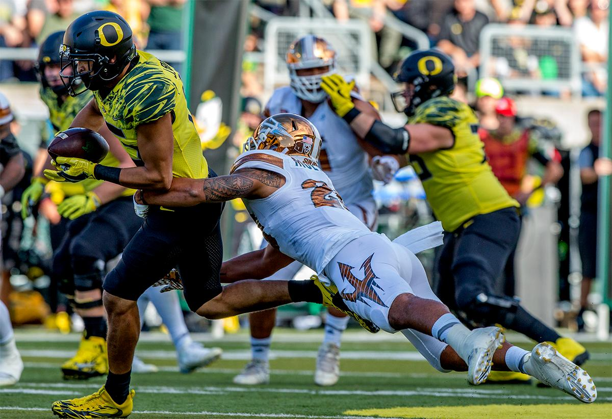 The Duck's Jalen Brown (#15) run the ball down the field as the Sun Devils attempt to stop him. The Oregon Ducks broke their losing streak by defeating the ASU Sun Devils on Saturday 54-35. Photo by August Frank, Oregon News Lab