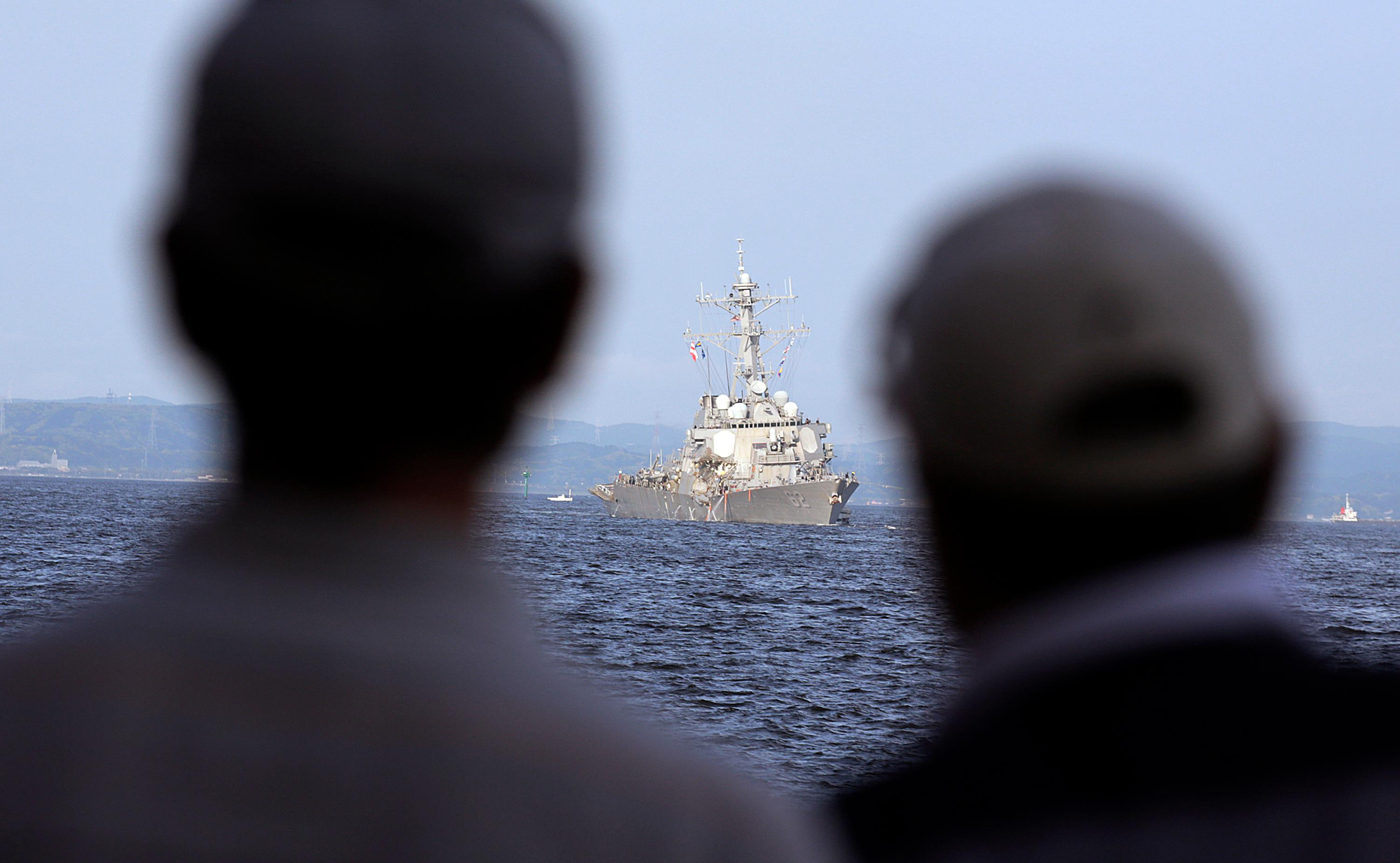People watch the damaged USS Fitzgerald being towed near the U.S. Naval base in Yokosuka, southwest of Tokyo, after the U.S. destroyer collided with the Philippine-registered container ship ACX Crystal in the waters off the Izu Peninsula Saturday, June 17, 2017. Crew members from the destroyer USS Dewey were helping stabilize the damaged USS Fitzgerald after its collision off the coast of Japan before dawn Saturday, leaving seven sailors missing and at least three injured. (AP Photo/Eugene Hoshiko)