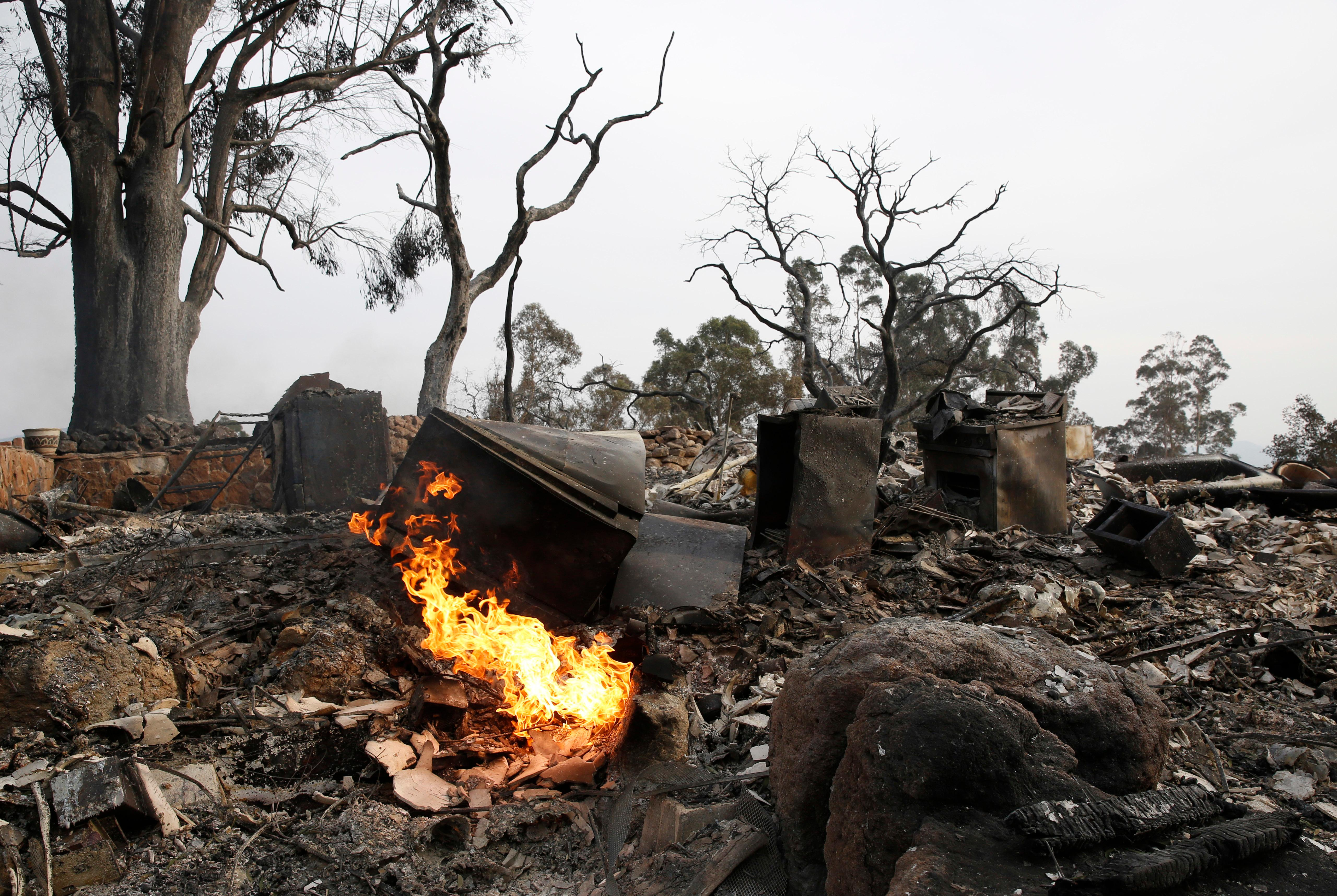 Flames fed by a gas line, burns in the debris of a fire ravaged home, Tuesday, Oct. 10, 2017, in Napa, Calif. Wildfires whipped by powerful winds swept through the California wine country sending thousands fleeing as flames rages unchecked through high-end resorts, grocery stores and tree-lined neighborhoods.(AP Photo/Rich Pedroncelli)