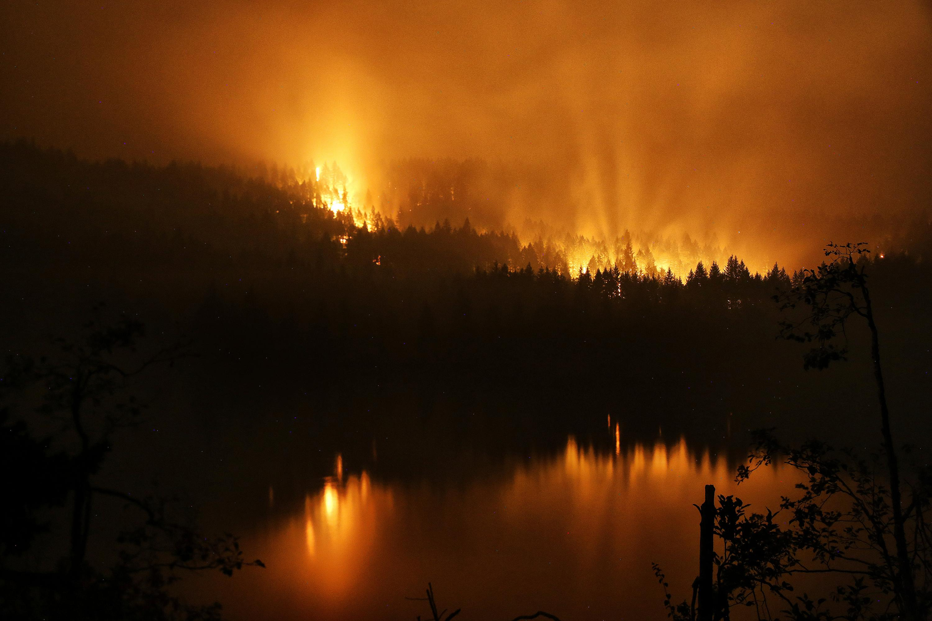 A wildfire continues to burn on the Oregon side of the Columbia River Gorge near Cascade Locks, Ore., and the Bridge of the Gods, late Tuesday, Sept. 5, 2017. (Genna Martin/seattlepi.com via AP)