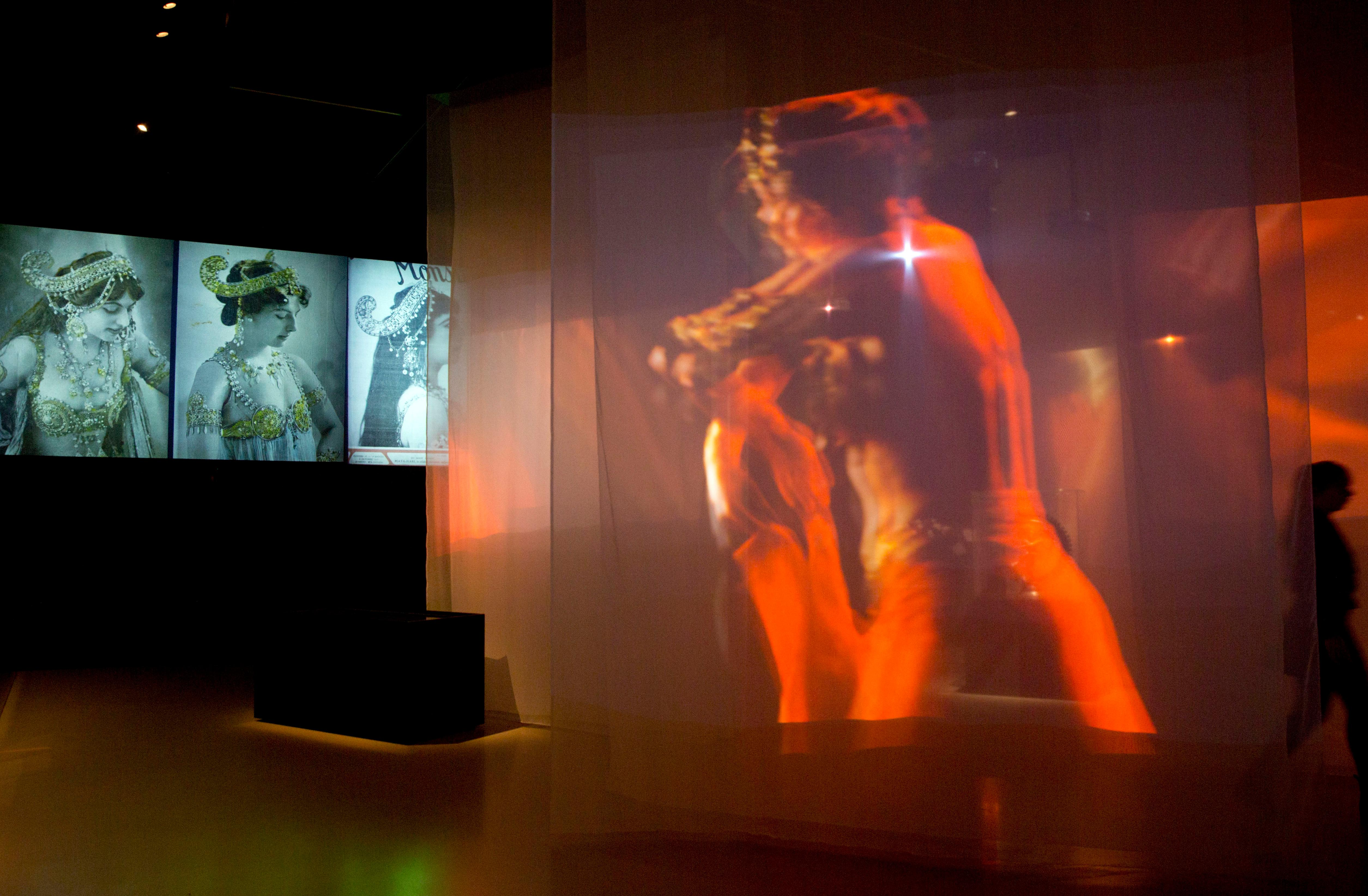 In this photo taken on Friday, Oct. 13, 2017, a visitor walks through a projection and photos of Margaretha Zelle, also known as Mata Hari, at the Fries Museum in Leeuwarden, Netherlands. A century ago, on Oct. 15, 1917, an exotic dancer named Mata Hari was executed by a French firing squad, condemned as a sultry Dutch double agent who supposedly led tens of thousands of soldiers to their death during World War I. (AP Photo/Virginia Mayo)
