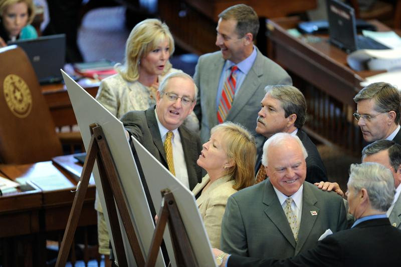 State representatives look at redistricting maps on the floor of the Texas House on April 27, 2011. (Photo by Bob Daemmrich via the Texas Tribune)