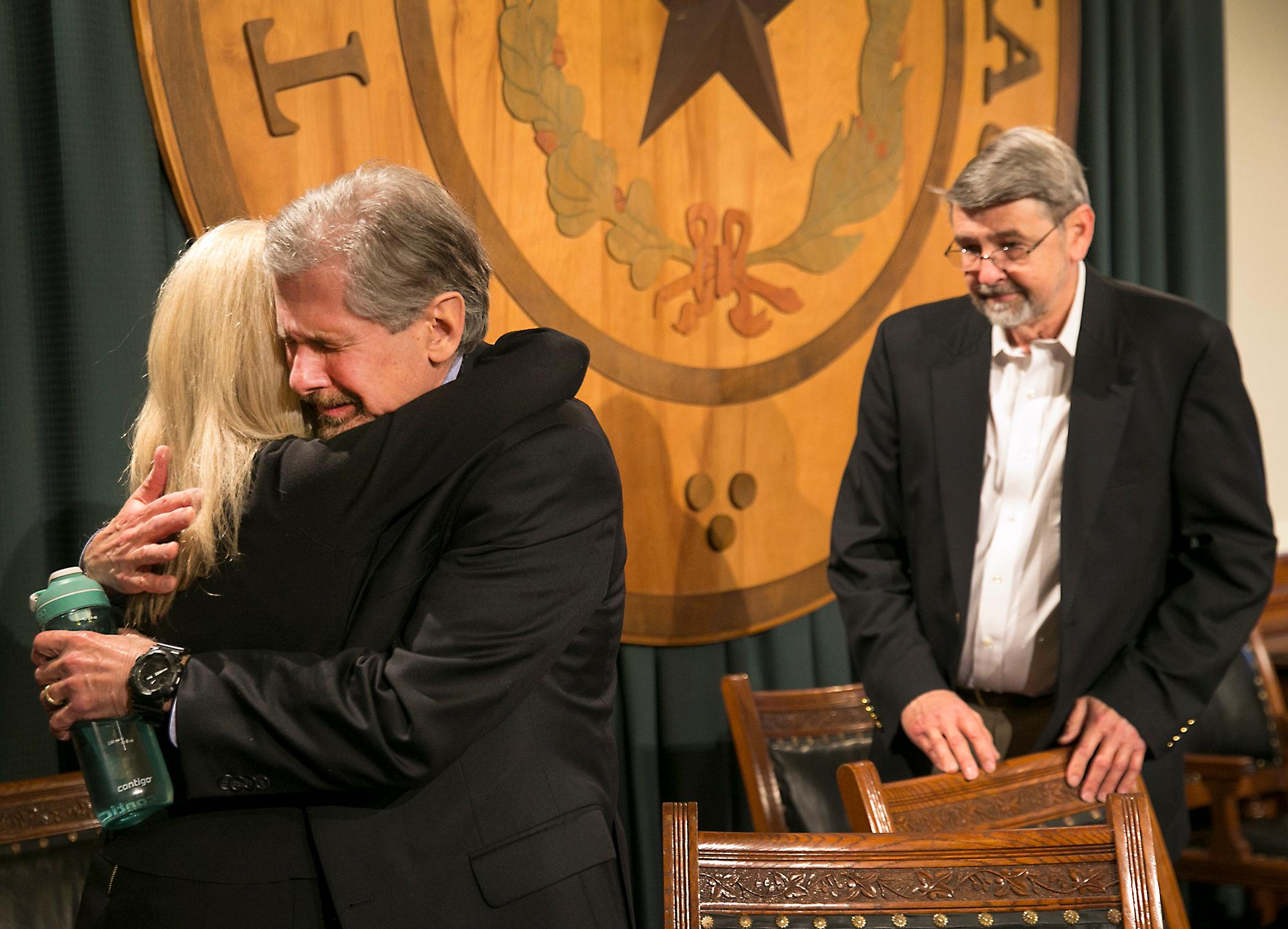 Kent Whitaker embraces his wife Tanya as his brother Keith Whitaker waits in support at back right, after reacting to the his lawyer Keith Hampton reading an email from the Texas Board of Pardons and Paroles which voted unanimously to recommend clemency for death row inmate Thomas Whitaker, Kent's son who was found guilty of setting up an ambush that killed his mother and brother in 2003. Despite the crime, his father had waged a desperate campaign to spare his life before Thursday's scheduled execution. The board recommended that Whitaker's sentence be reduced to life in prison as they read the reaction Tuesday, Feb. 20, 2018, in Austin, Texas. (Ralph Barrera/Austin American-Statesman via AP)