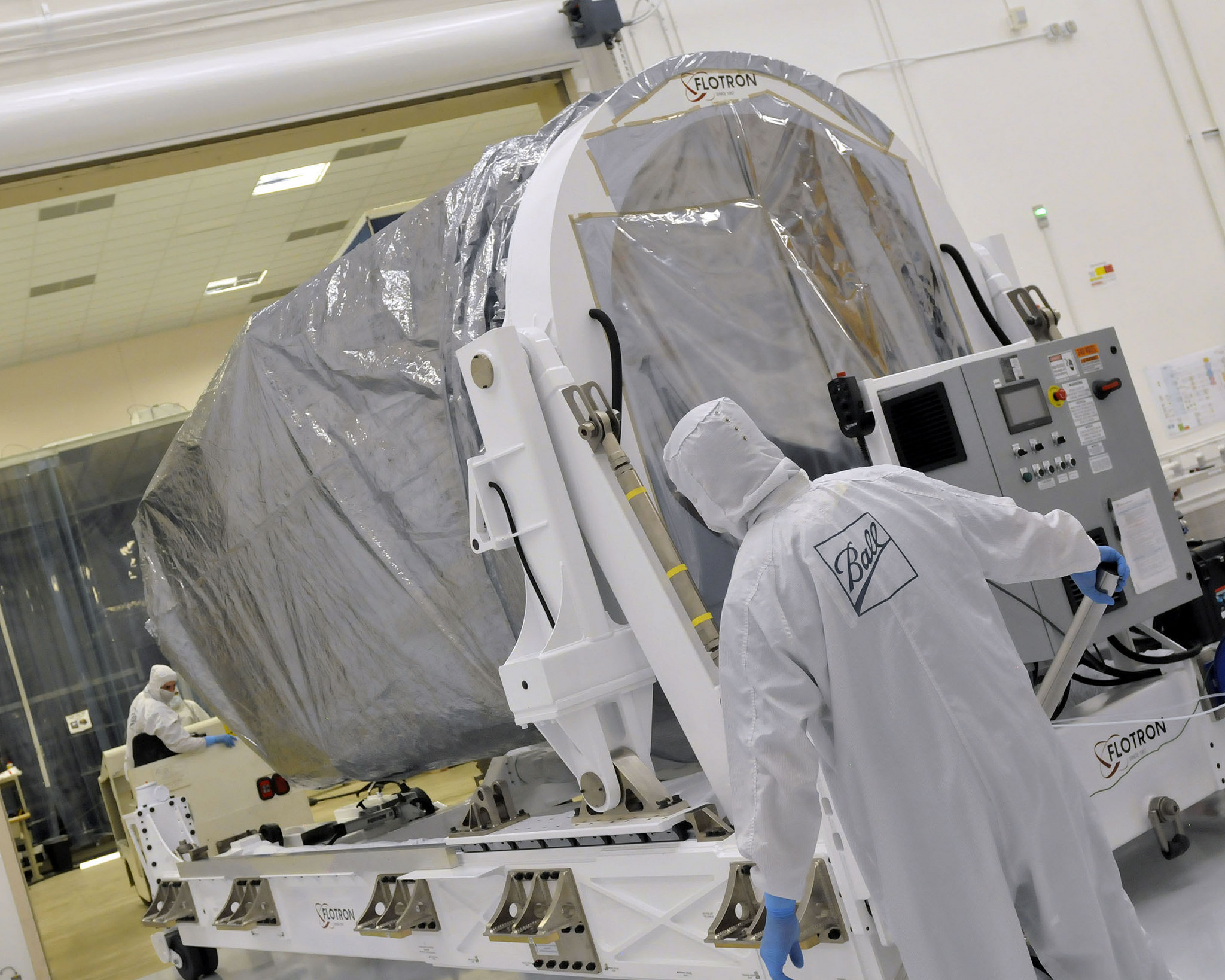 Ball Aerospace engineers and technicians transport the JPSS-1 satellite to its shipping container. Even though the satellite weighs 5,000 pounds (or 2.5 tons), transporting the spacecraft is a delicate operation. One wrong move could damage JPSS-1's sensitive instruments. (NASA Photo)