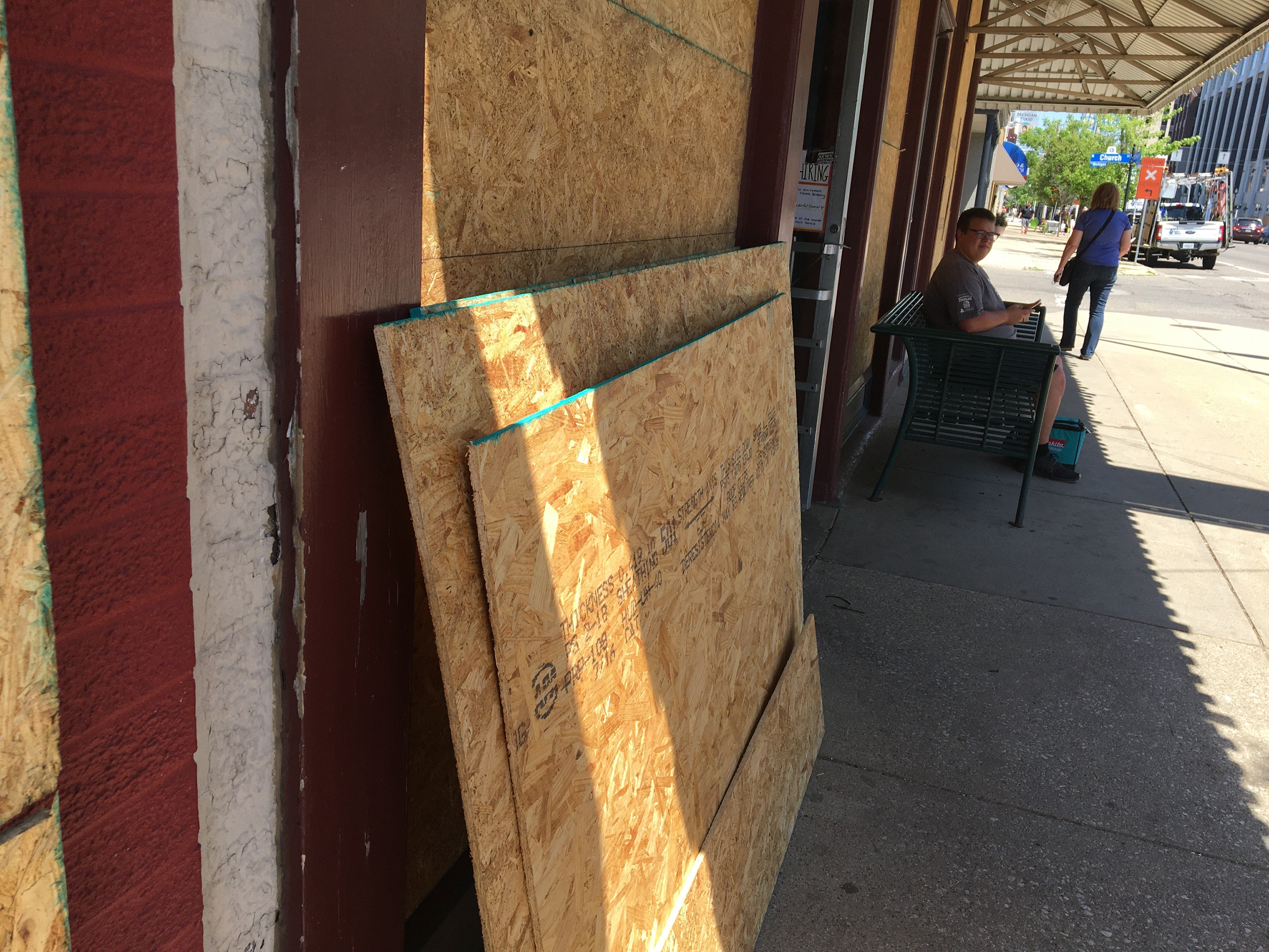 Press board rests against a downtown Kalamazoo building as work crews begin covering windows and doors of shops and businesses along the main streets and in the Kalamazoo Mall on Tuesday, June 2, 2020. (WWMT/Manny Revilla)
