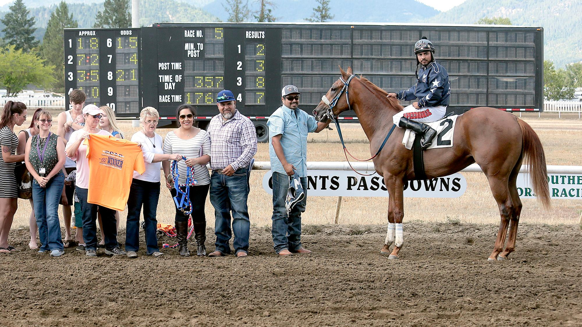 Harem Bar Cartel, with jockey Ruben Lozano, Trainer Danny S. Montes (standing far right) and Owner Jorge L. Camona (standing second right) after finishing with the fastest qualifying time for the Firecracker Futurity at Grants Pass Downs on Sunday. [PHOTO BY:  LARRY STAUTH JR]