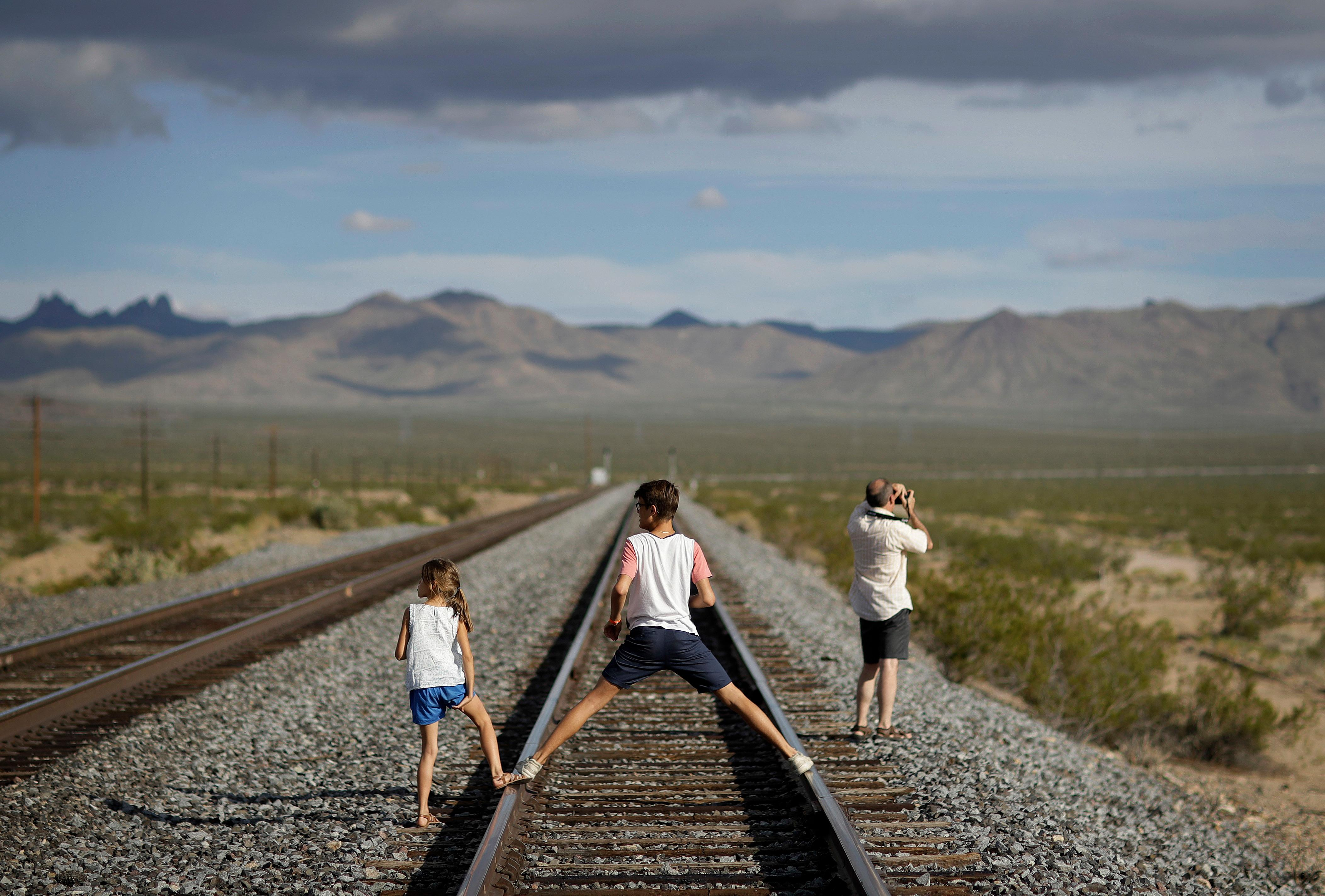 A family walks along train tracks, Thursday, Aug. 3, 2017, in Nipton, Calif. One of the nation's largest cannabis companies announced it has bought the entire 80 acre California desert town of Nipton. (AP Photo/John Locher)