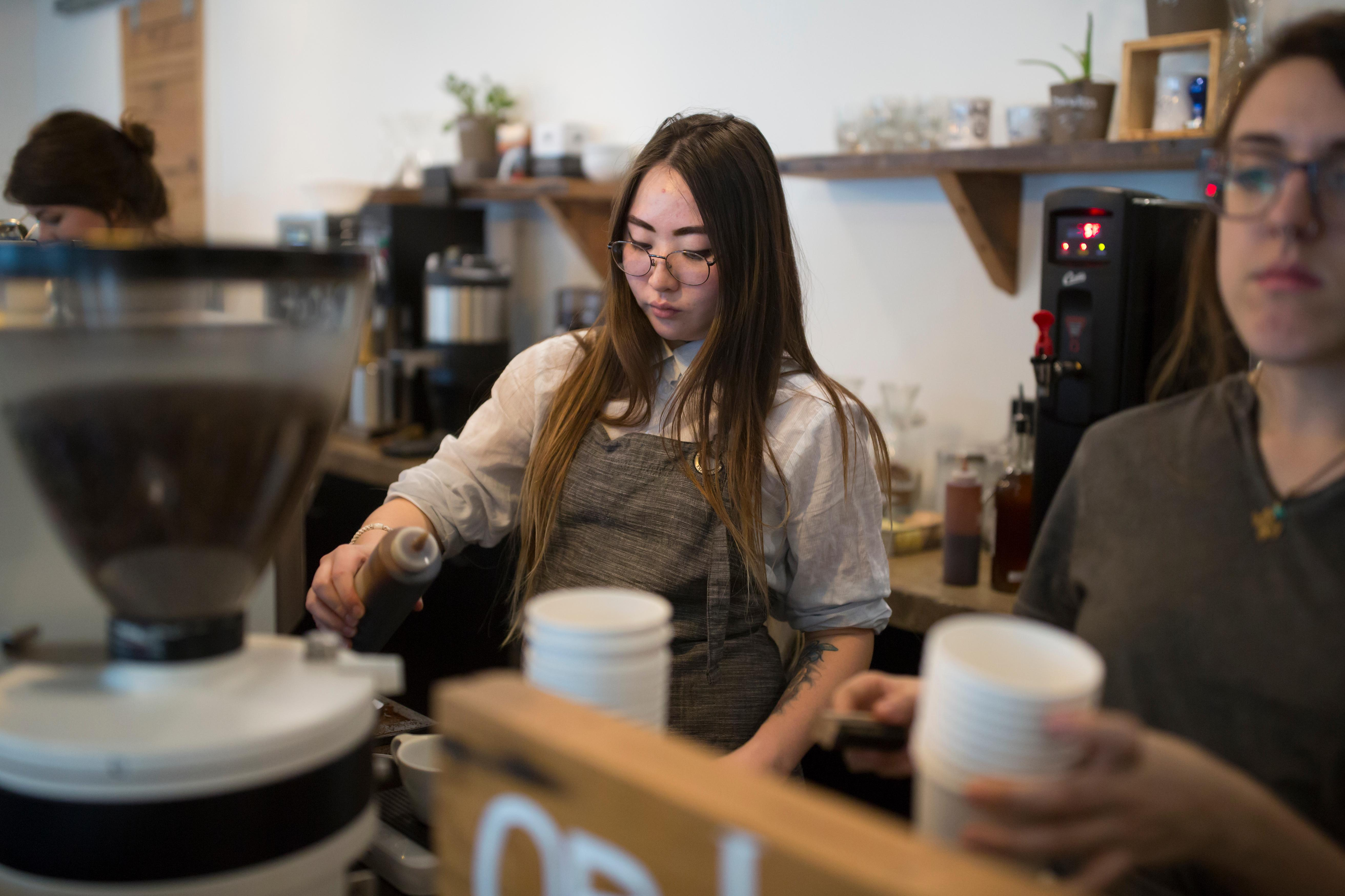 22-year-old Ynga Chernogradskaia makes a cup of coffee for a customer at Street Bean Coffee Roasters, a local coffee shop and non-profit that's dedicated to providing work opportunities for street-involved youth. Chernogradskaia became homeless after coming to the U.S. in September 2016, but found work through the program and is now living on her own. (Sy Bean / Seattle Refined)
