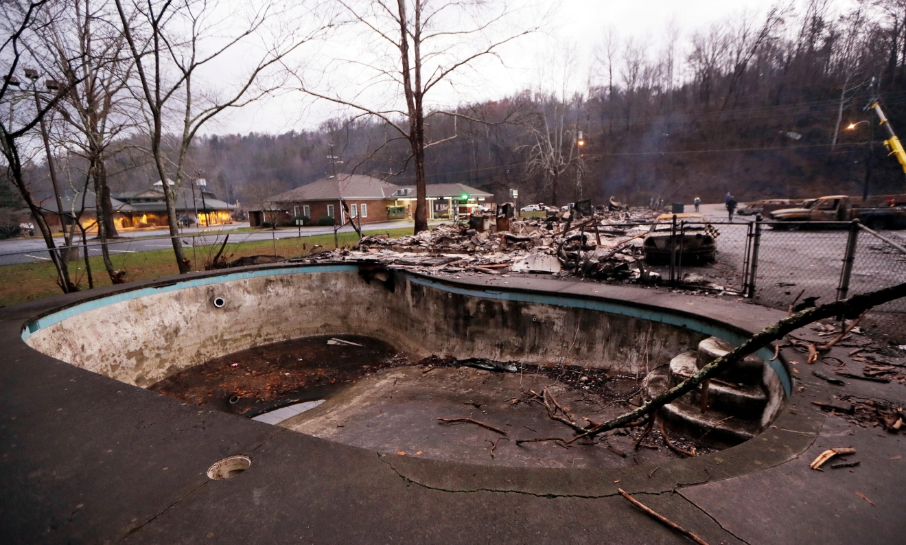 A swimming pool in a motel complex shows burn marks Wednesday, Nov. 30, 2016, in Gatlinburg, Tenn., after a wildfire swept through the area Monday. Three more bodies were found in the ruins of wildfires that torched hundreds of homes and businesses in the Great Smoky Mountains area, officials said Wednesday. (AP Photo/Mark Humphrey)