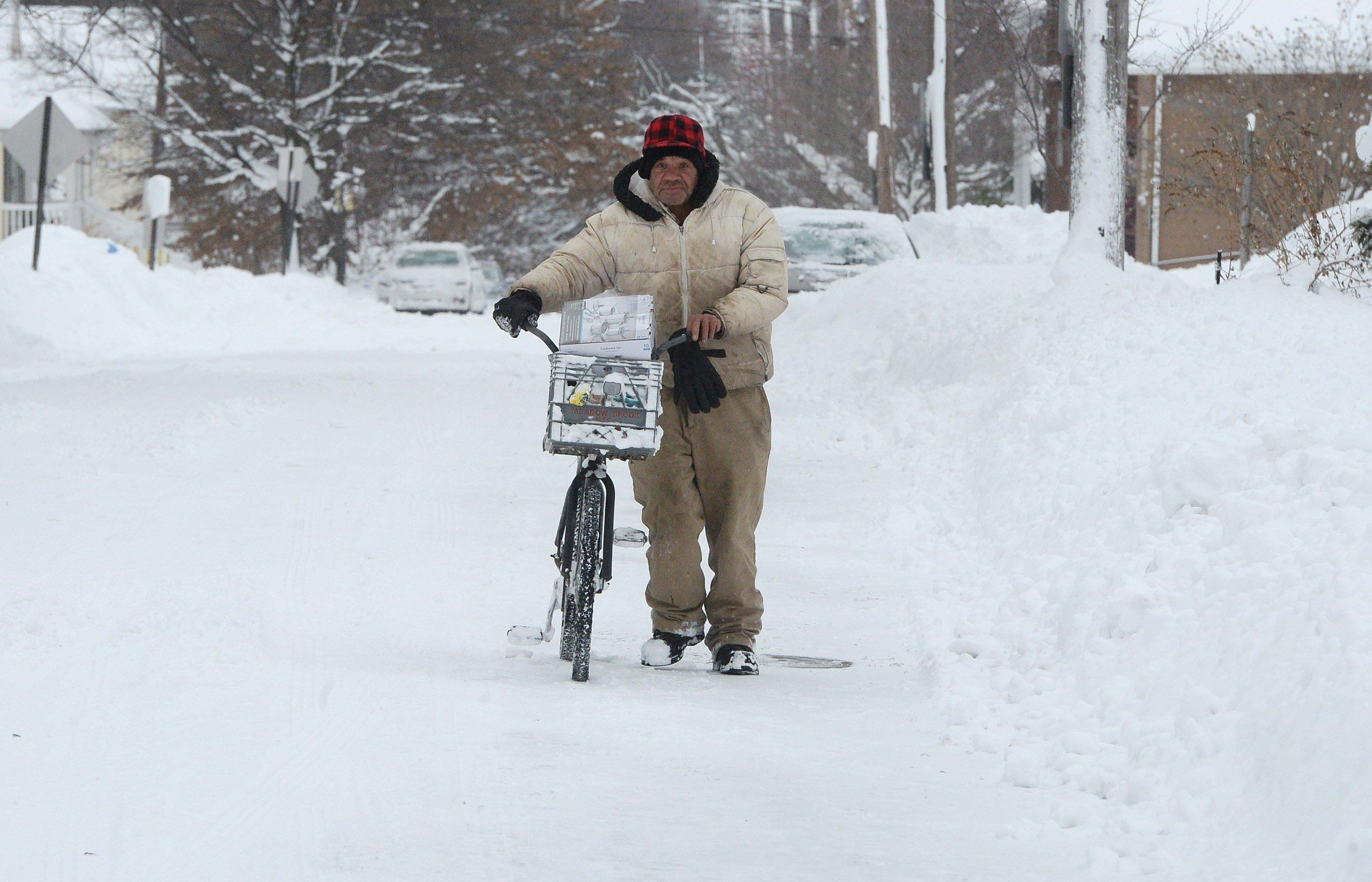 Logan Rogers pushes his bike along East Third Street in Erie, Pa., Wednesday, Dec. 27, 2017. Freezing temperatures and below-zero wind chills socked much of the northern United States on Wednesday, and the snow-hardened city of Erie, dug out from a record snowfall.  (Jack Hanrahan/Erie Times-News via AP)
