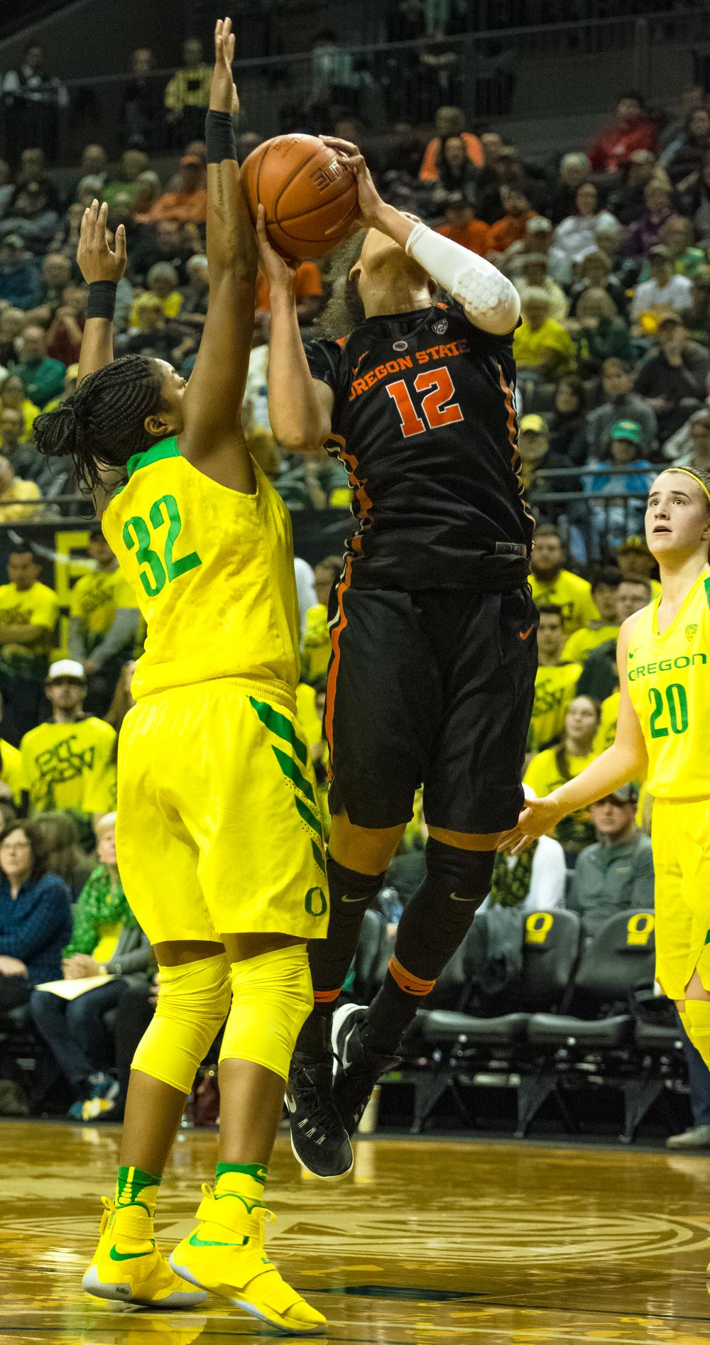 Oregon Ducks Forward Oti Gildon (#32) defends against Oregon State Forward Kolbie Orum (#12) to stop the easy layup. Oregon Ducks lost 40-43 to Oregon State Beavers in a tightly matched fourth quarter. Photo by Jonathan Booker, Oregon News Lab