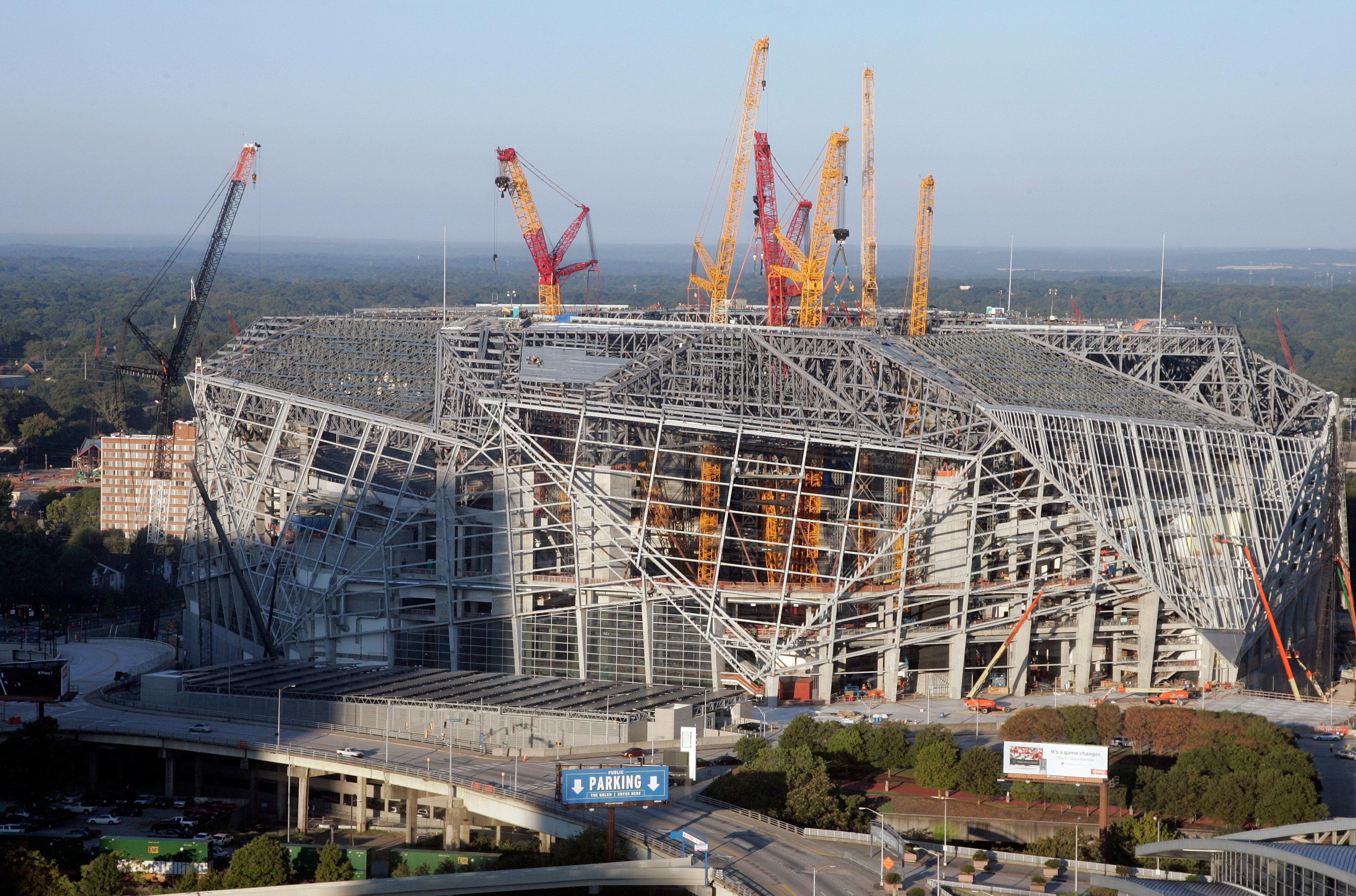 "In this Sept. 24, 2016 photo, construction crews work on the the Mercedes-Benz stadium, in Atlanta. The new $1.5 million stadium is home to the National Football League's Atlanta Falcons and Major League Soccer's Atlanta United. It features a retractable roof; a 1,100-foot ""halo board"" video display; and a giant steel sculpture of a Falcon with its 70-foot wingspan at one of the main entrances. (AP Photo/John Bazemore)"