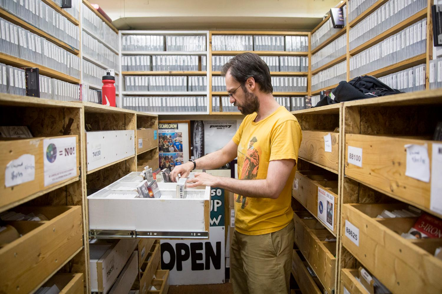 Every day, Inventory Manager Joel Fischer organizes the massive collection of titles at Scarecrow Video, the film rental store that has been serving Seattle for over 30 years. In 2014, the collection had grown to become such a significant archive that a non-profit was formed. The store continues to grow at a rate of 3,000-5,000 titles each year, representing 129 countries and over 126 languages. (Sy Bean / Seattle Refined)