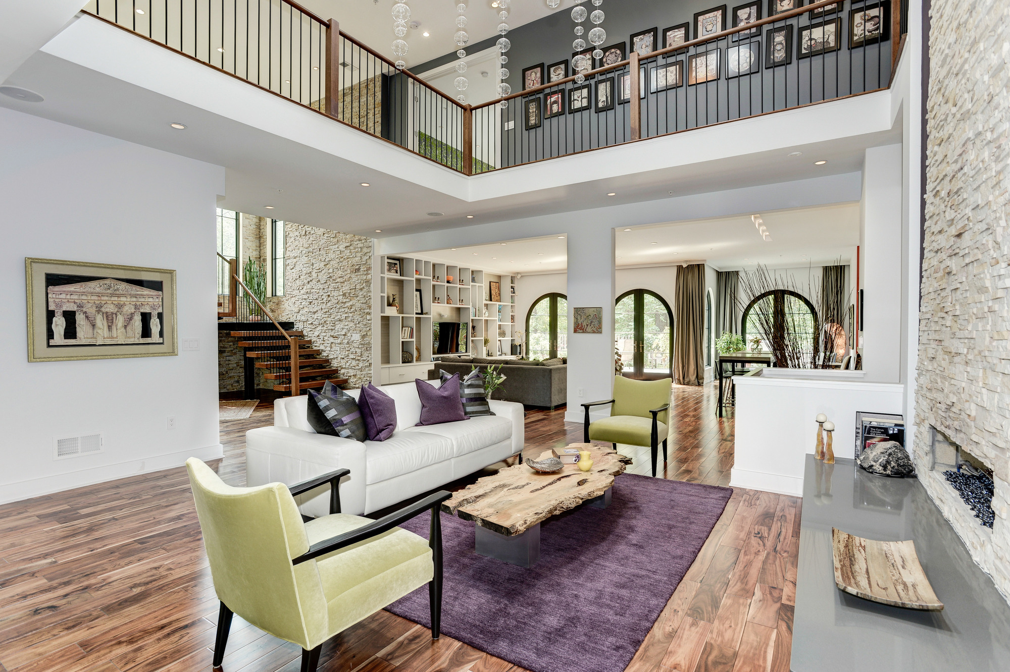 This five-bedroom/seven-bath contemporary home, which recently dropped in price by $150,000, is a rare find in Bethesda! Its European flair can be seen throughout the home from the Spanish cedar front door to the strong penchant for color, soaring ceilings and wide variety of natural materials and textures used. For example, the stacked stone walls and chimney and blonde accacia  wood floors truly create warmth not always associated with contemporary style. The open design is balanced by the aesthetically pleasing definition of spaces through use of architectural elements such as arched doors and windows. The two-story living room also draws the eye in, with a stacked stone fireplace (the stonework is angled for additional interest) and the built-in media wall in the family room is accented by contrasting textured treatments. The property is listed by Meg Percesepe and Alison Shutt of Washington Fine Properties, and is in a great location, situated between downtown Bethesda and Potomac Village. Tour the rest of the house in our gallery and visit WFP.com for more info on the property! (Image: HomeVisit)