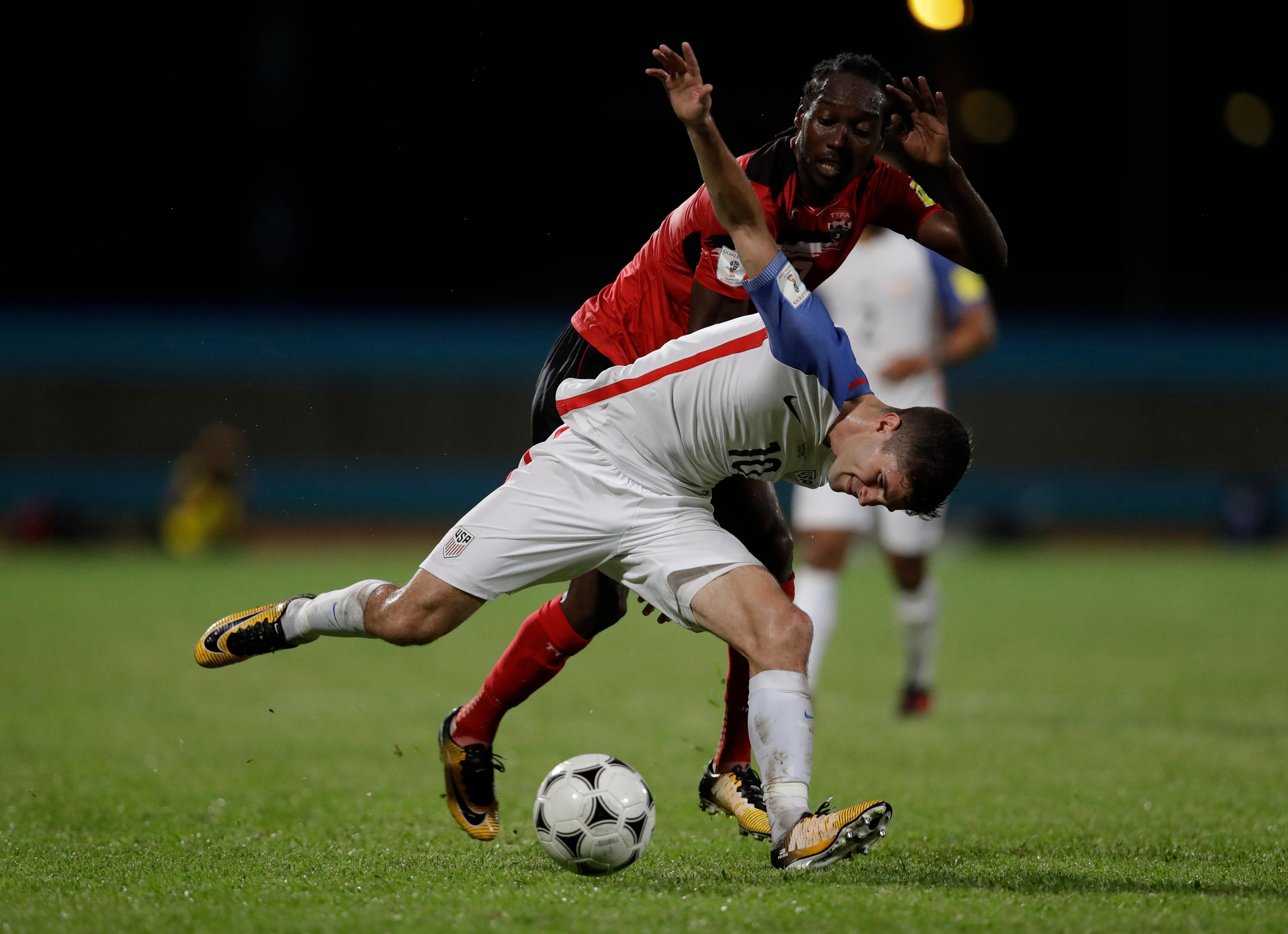 United States' Christian Pulisic, front, fights for control of the ball with Trinidad and Tobago's Nathan Lewis during a 2018 World Cup qualifying soccer match in Couva, Trinidad, Tuesday, Oct. 10, 2017. (AP Photo/Rebecca Blackwell)