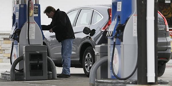 A man checks gas prices at a Mobil gas station in Chicago. Gasoline prices are climbing as rising economic growth boosts oil prices and temporary refinery outages crimp gasoline supplies on the East and West Coasts. - AP