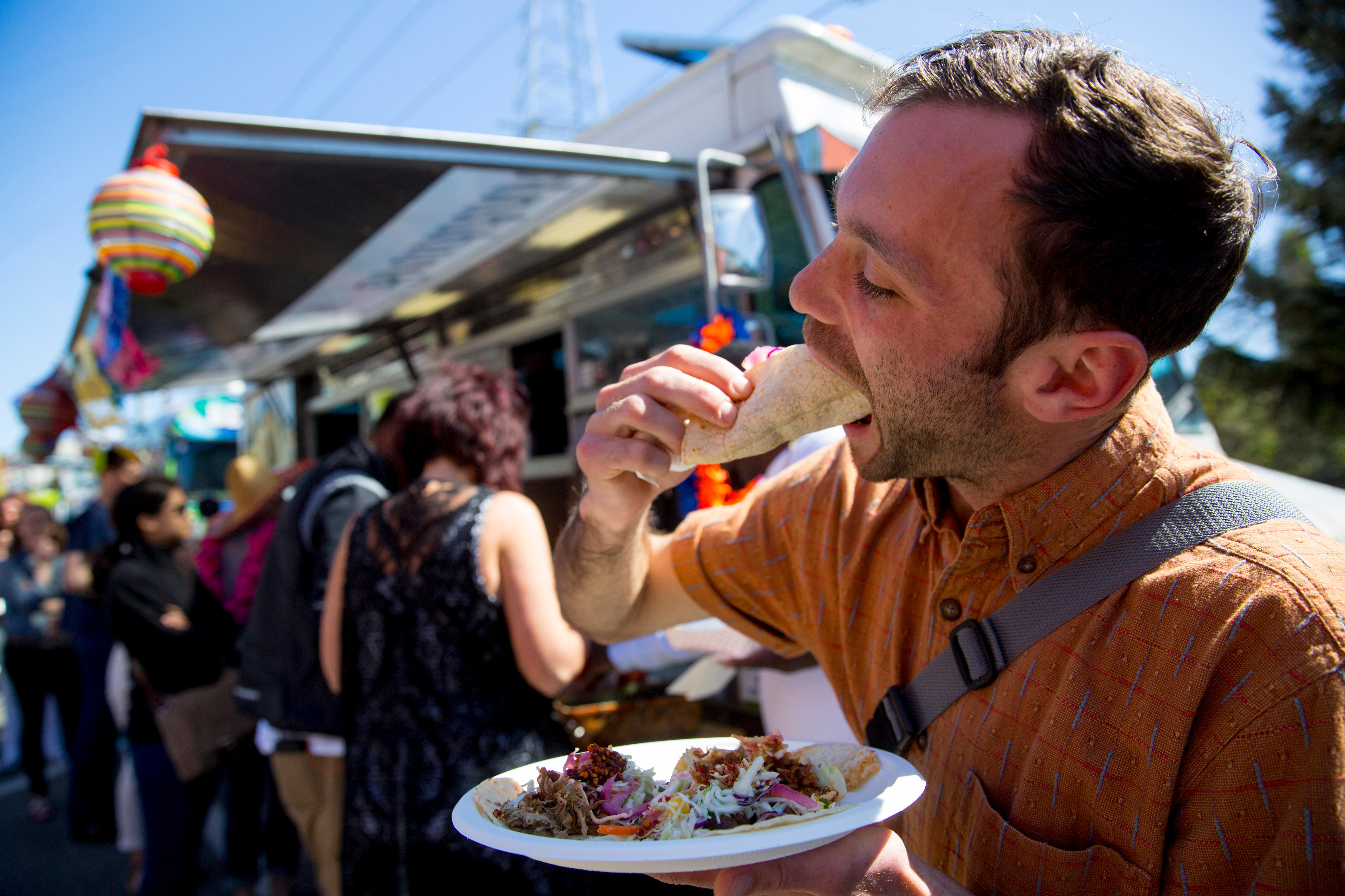 Jasper Knox munches down on a Señor Buddha Bruddah taco at the 5th Annual Taco Libre Taco Truck Showdown Challenge at the Fremont Market. (Sy Bean / Seattle Refined)