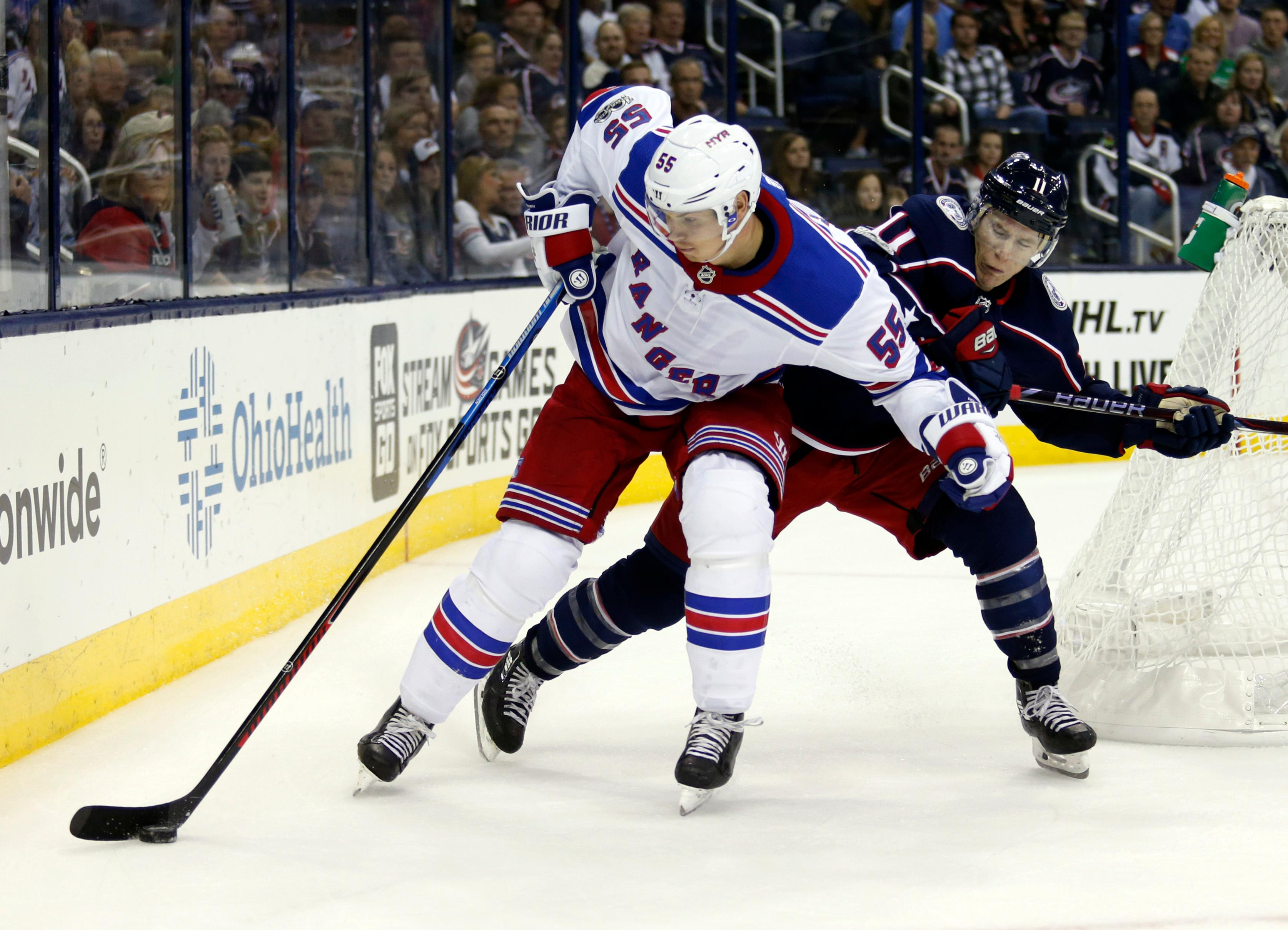New York Rangers defenseman Nick Holden, left, works against Columbus Blue Jackets forward Matt Calvert during the second period of an NHL hockey game in Columbus, Ohio, Friday, Oct. 13, 2017. (AP Photo/Paul Vernon)