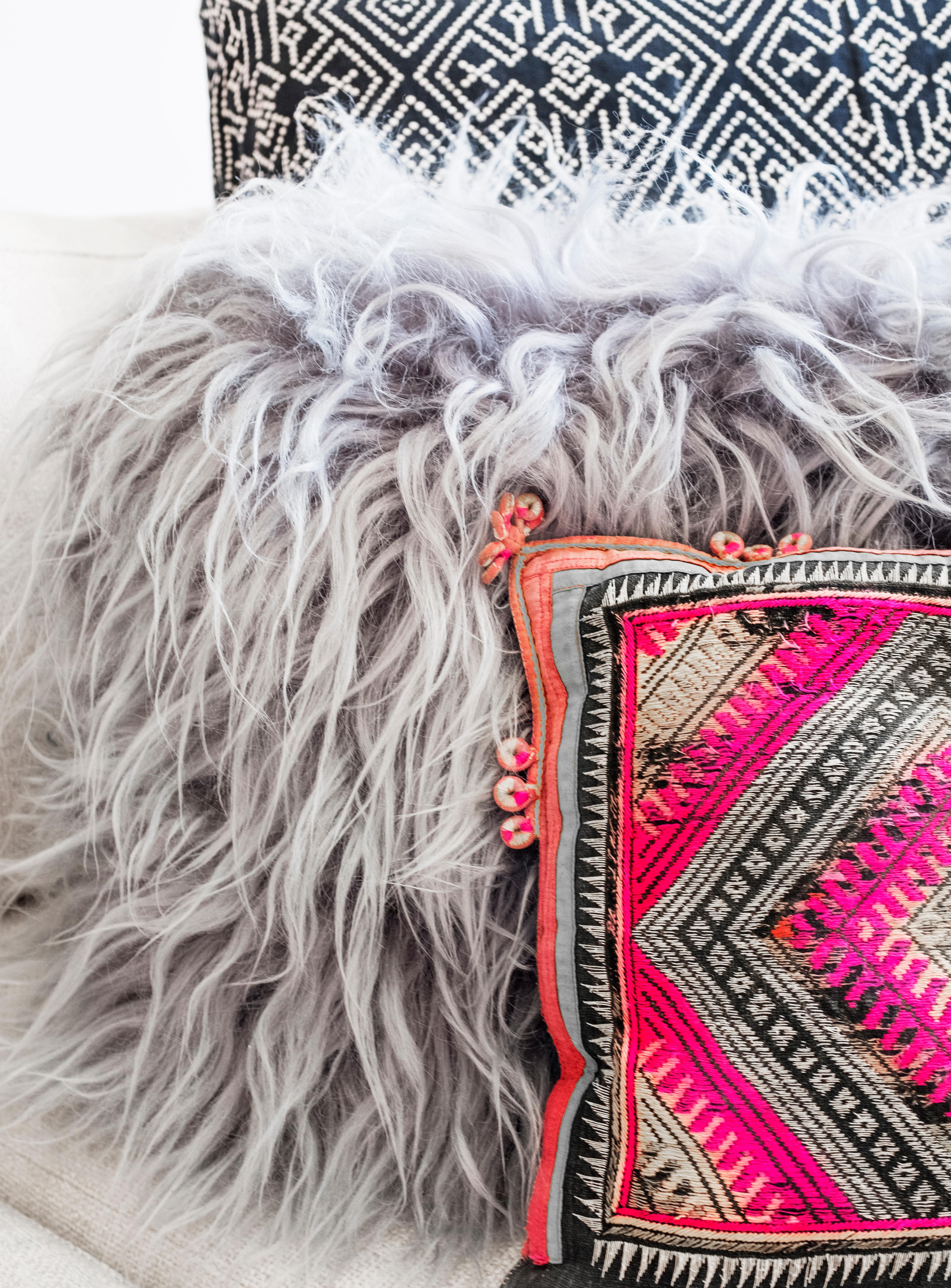 Spring is very much a transitional time for your living room. Bring a bit of color inside and mix it with a few of your wintery pieces such as a faux fur pillow, cable knit pillow or throw. (Image: Ashley Hafstead)